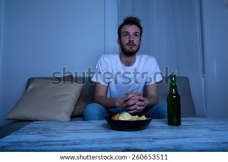 A young man watching TV at nighttime with potato chips and beer at home in the living room.  - stock photo