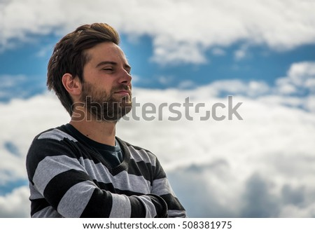 A young man wearing a black and gray sweater climbs on top of the building white clouds behind with a nice blue sky Brown hair and a beard
