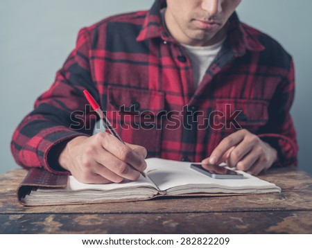 A young man wearing a checkered jacket is using a smartphone and is taking notes in a notebook at a desk