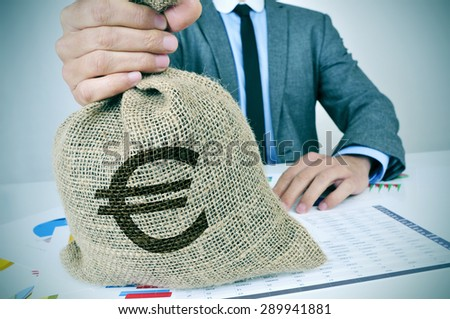 a young man wearing a gray suit seated at an office desk full of charts and financial balances holds a burlap money bag with the euro currency sign in his hand - stock photo
