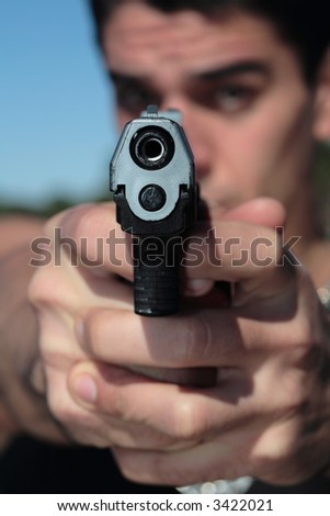 A young man, wearing a sleeveless shirt, holding a hand gun. (This image is part of a series)