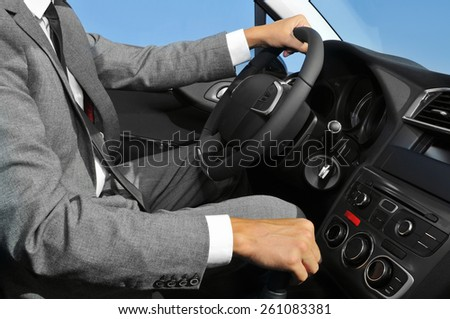a young man wearing a suit driving a car with manual transmission - stock photo