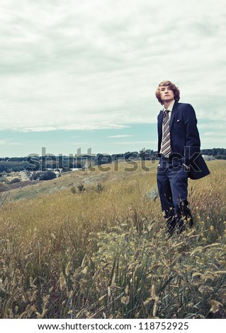 A young man wearing business attire standing on a hill. - stock photo