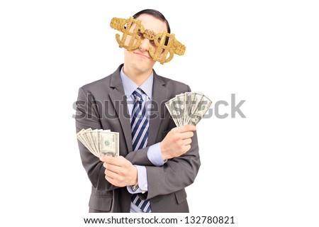 A young man wearing dollar sign glasses and holding US dollars isolated on white background - stock photo