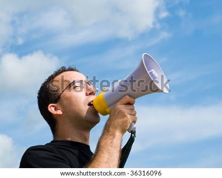 A young man wearing glasses is talking into a megaphone outside with blue sky behind him - stock photo