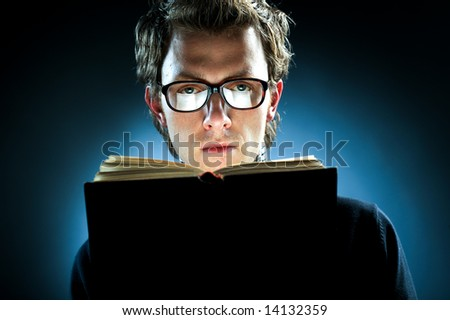 A young man wearing spectacles reading a book - stock photo