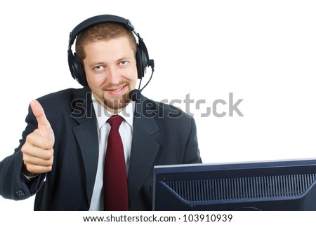 A young man wearing suit and tie, headset on his head, smiling and showing his thumb up, sitting behind a monitor, looking into the camera - isolated on white - stock photo