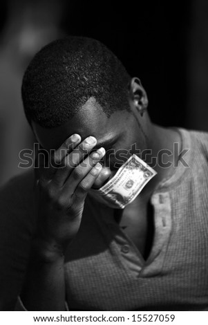 a young man wears a dollar bill taped over his mouth in protest against inflation and the rising cost of goods and services in black and white - stock photo