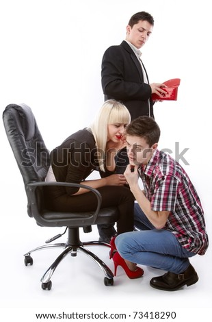 A young man who looks at a woman's purse who discuss something in secret with another young man. - stock photo