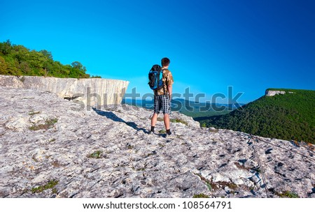 A young man with a backpack standing on the hill against the blue sky - stock photo