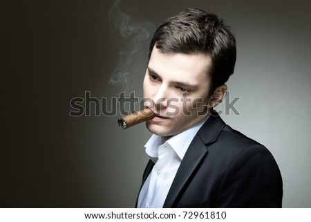 A young man with a cigar looking contemplative - stock photo