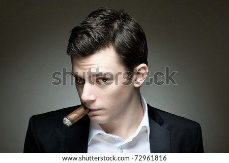 A young man with a cigar looking doubtful - stock photo