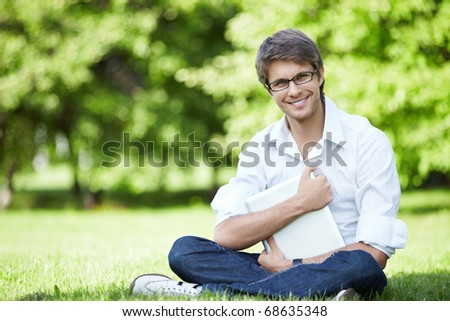 A young man with a computer in the park - stock photo
