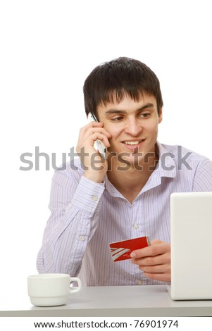 A young man with a credit card in front of a laptop, talking on the phone - stock photo