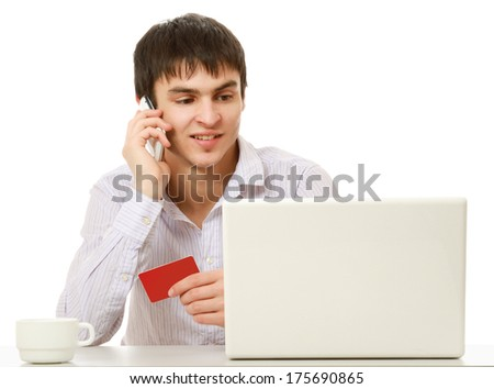 A young man with a credit card in front of a laptop, talking on the phone, isolated on white background