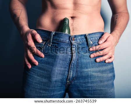 A young man with a cucumber stuffed down his pants - stock photo