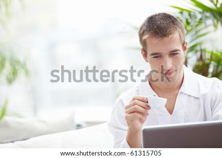 A young man with a cup and a laptop in a restaurant - stock photo