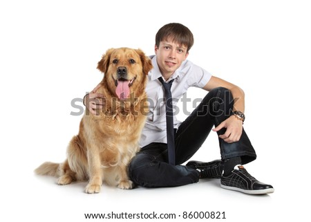 A young man with a dog breed golden retriever sitting on floor, looking at camera