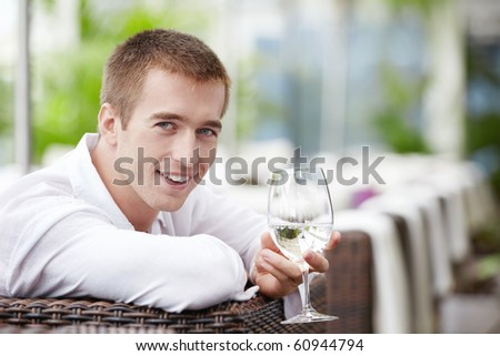 A young man with a glass in the cafe - stock photo