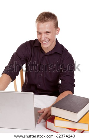 A young man with a happy expression enjoying studing on his computer with a stack of books next to him. - stock photo