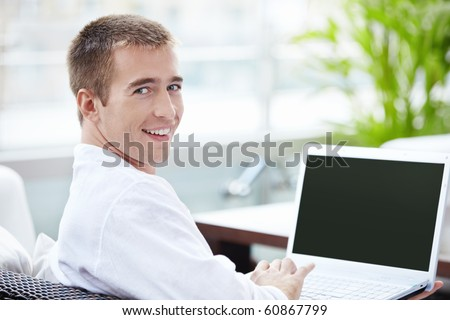 A young man with a laptop in a cafe - stock photo