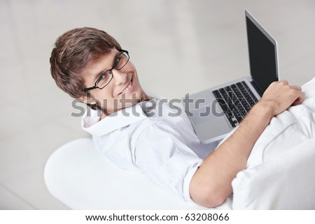 A young man with a laptop on a couch - stock photo