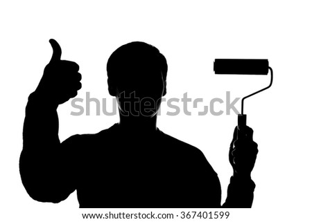A young man with a paint roller in his hand - silhouette