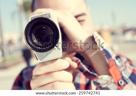 a young man with a plaid shirt filming with a Super 8 camera outdoors - stock photo
