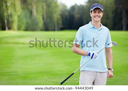 A young man with a stick on the golf course - stock photo