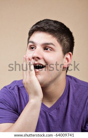 A young man with a surprised look on his face puts his hand on his cheek. - stock photo