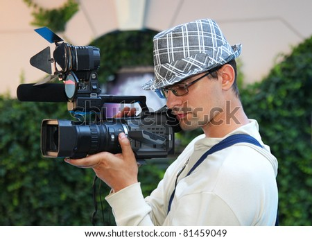 A young man with a video camera - stock photo