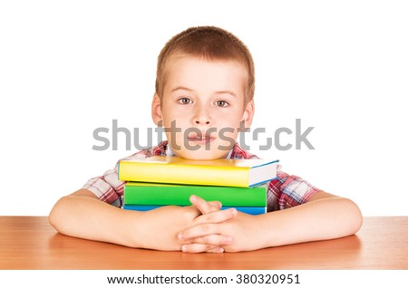 A young man with books at the desk isolated on white background - stock photo