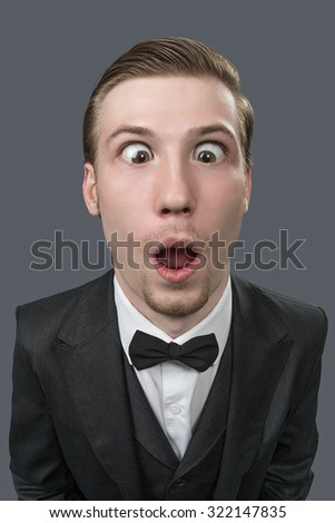 A young man with bulging eyes squinting. Studio photo, gray background. - stock photo