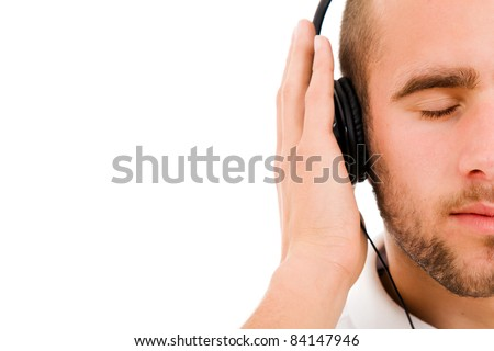 a young man with eyes closed listening to music with headphones, isolated on white - stock photo