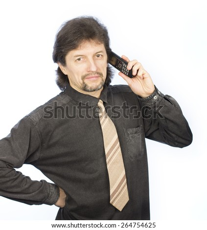 A young man with long hair in a black shirt is emotionally talking on the phone
