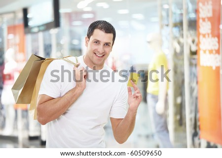 A young man with the shopping and credit card at the store - stock photo