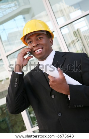 A young man working as an architect on a building site - stock photo