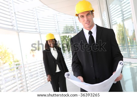 A young man working as architect on a construction site with coworker in background - stock photo