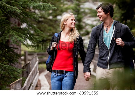 A young mand and woman walking in the forest - stock photo