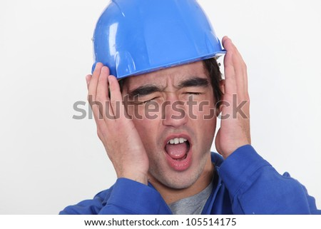 A young manual worker hearing unbearable noise. - stock photo