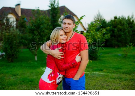 a young married couple in the garden. autumn. at sunset - stock photo