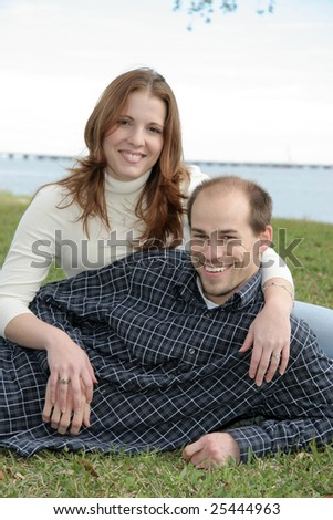 A young married couple sit in the grass enjoying a park setting. - stock photo