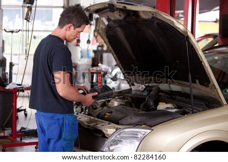 A young mechanic running a diagnostic test on a car - stock photo