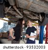 A young mechanic showing a female customer what was done to her car - stock photo