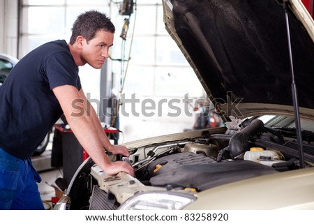 A young mechanic staring at a car, thinking - stock photo