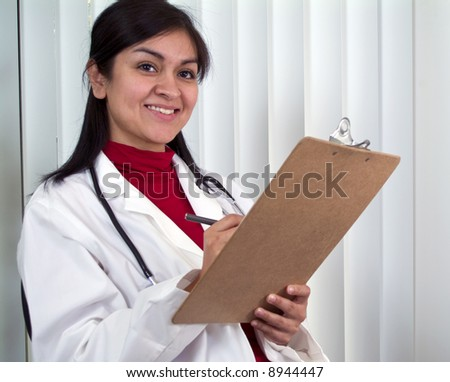 A young medical professional with a chart in her hand with big smile on her face. - stock photo