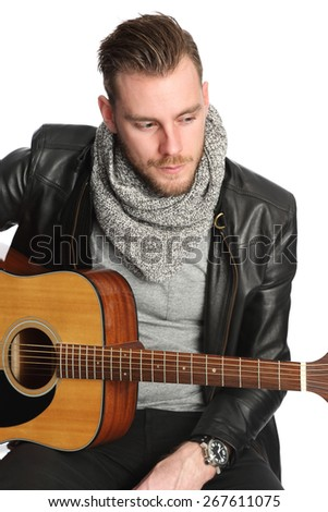 A young modern and attractive man wearing a black leather jacket and grey shirt sitting down playing on an acoustic guitar. White background. - stock photo