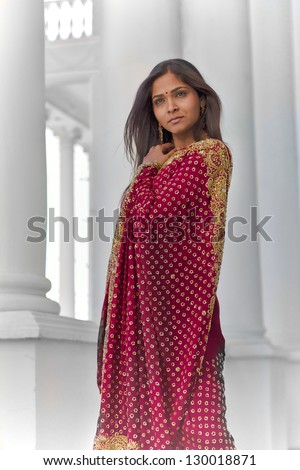 A young, modern, 30 something, Indian woman with long black hair, dressed in traditional Indian attire (saree), stands near tall white columns for a dramatic and elegant portrait on a bright sunny day - stock photo