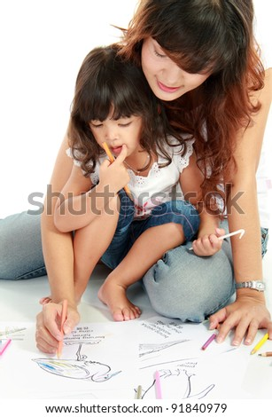 a young mom and her little daughter drawing together, isolated over white background - stock photo