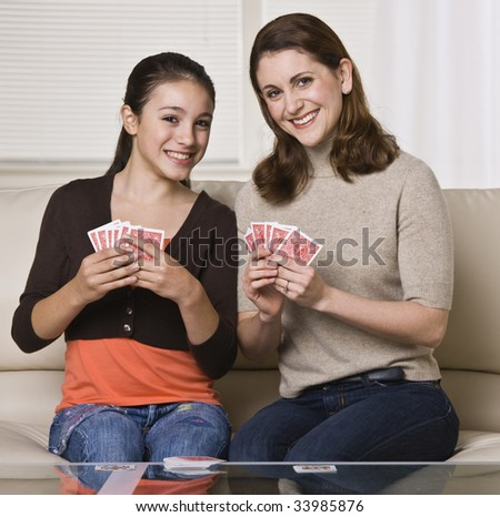 A young mother and her daughter are playing cards together.  They are smiling at the camera.  Square framed shot. - stock photo
